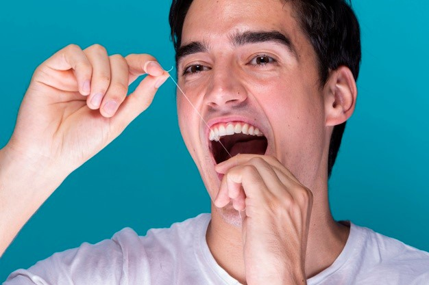 A man holding opening his mouth and holding a dental floss vertically