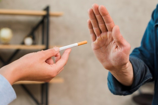 man refusing an offer to smoke by a showing disapproval through his hand