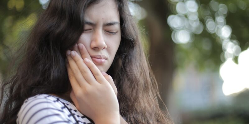 Photo of woman experiencing tooth sensitivity and bleeding gums in black and white stripe shirt pressing her cheek
