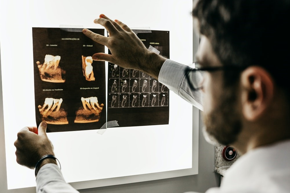 A male dentist holding up teeth scans against a tablet computer