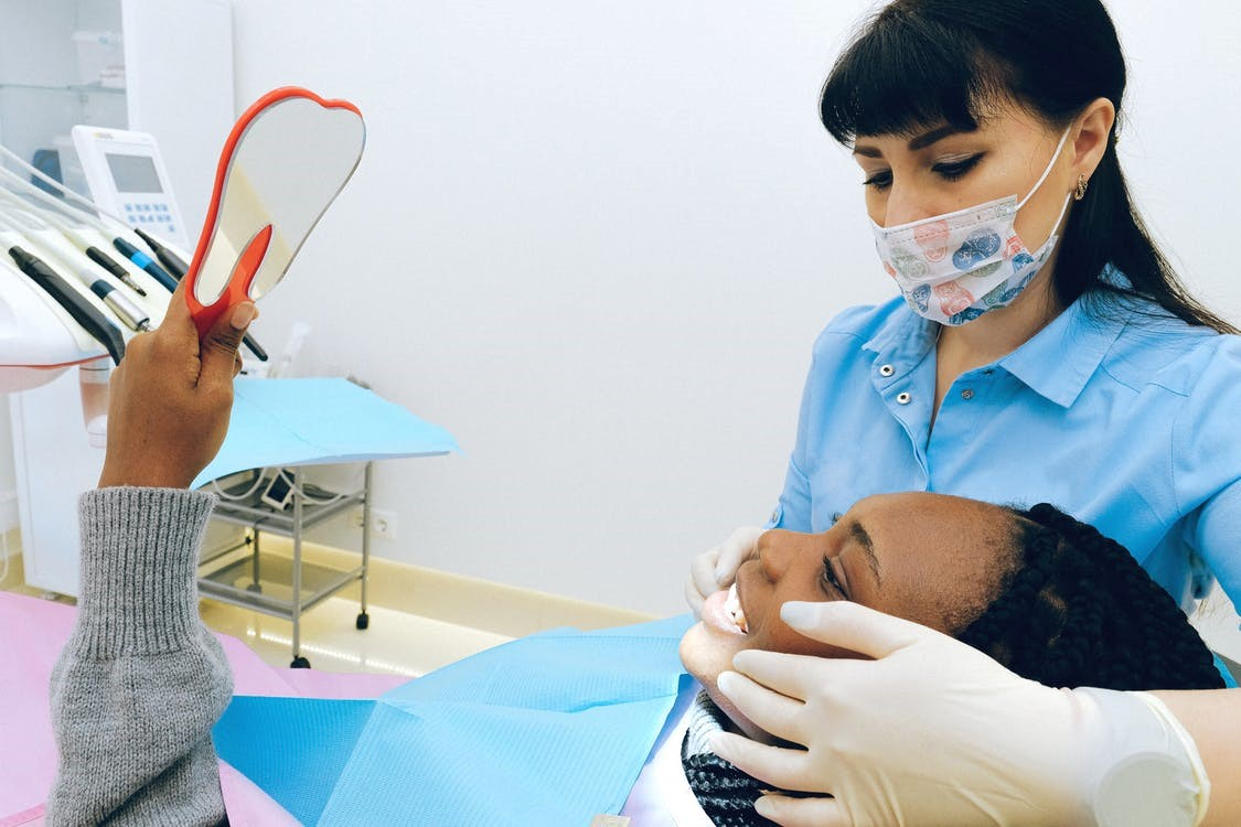 A patient looking at her teeth after a dental procedure