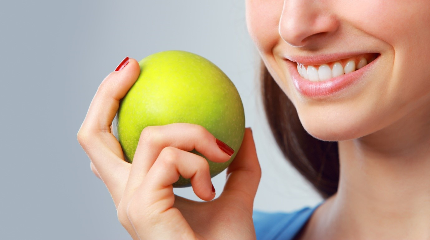 a woman holding a green apple and grinning